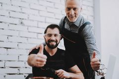 Two Exited Smiling Men in Uniform in Workshop. royalty free stock photography