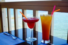 Two exotic cocktails on table, sea background stock image