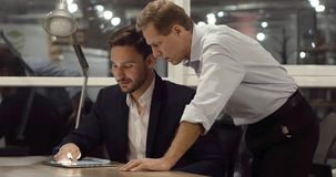 Two experienced businessmen. Two handsome partners are discussing results of the project in late office. Late work overtime concept stock video footage