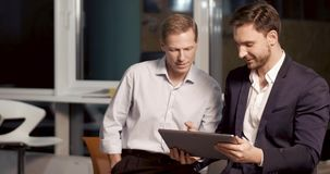 Two experienced businessmen. Two partners are looking at the tablet screen and discuss data of new project. Late work overtime concept stock footage