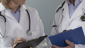 Two experienced doctors discussing strategy of treating seriously ill patient. Stock footage stock video