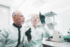 Two experienced genetics researchers standing near glass board. Glass board. Two experienced genetics researchers feeling busy while standing near glass board in stock photo