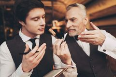 Two experienced sommeliers taste red wine and make wine list in restaurant. Confident sommelier checks aging of wine stock image