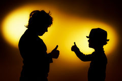 Two expressive boy's silhouettes showing emotions using gesticu stock images