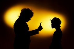Two  expressive boy's silhouettes showing emotions using gesticu. Lation, isolated on yellow Royalty Free Stock Image