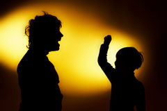 Two  expressive boy's silhouettes showing emotions using gesticu. Lation, isolated on yellow Stock Photography