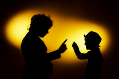 Two  expressive boy's silhouettes showing emotions using gesticu. Lation, isolated on yellow Stock Photo