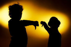 Two  expressive boy's silhouettes showing emotions using gesticu. Lation, isolated on yellow Royalty Free Stock Photography