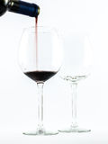 Two exquisite transparent glasses with red wine and a bottle pouring wine on a white background Royalty Free Stock Photos