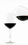 Two exquisite transparent glasses with red wine - one pouring wine into the other - on a white background Royalty Free Stock Photo