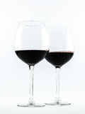Two exquisite transparent glasses with red wine on a white background Royalty Free Stock Image