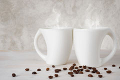 Two extraordinary white coffee cups on wooden table Royalty Free Stock Photos