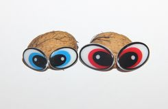Two eyed creatures on a white background, handmade from natural material. Two big-eyed creatures on a white background, crafts from natural materials, walnut stock photo