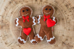 Two fabric gingerbread with hearts on wooden background, funny love story on valentines day Stock Images