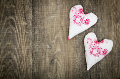 Two fabric hearts on brown wood floor Stock Images