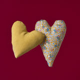Two fabric hearts on a red background. Stock Photography