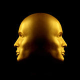 Two-faced gold head statue. Two faced gold head statue against black Royalty Free Stock Images