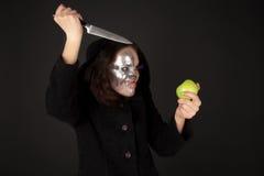 Two-faced Hexe mit grünem Apfel- und Küchemesser Lizenzfreie Stockbilder