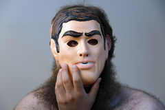 Two Faced Mask. A creepy man wears his mask on the side of his face Royalty Free Stock Photos