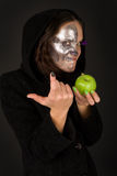 Two-faced sorceress with green apple tempts. Two-faced scary sorceress with green apple tempts Royalty Free Stock Image