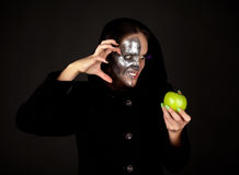 Two-faced witch with green apple grinning. Two-faced witch in black coat with green apple grinning Stock Image