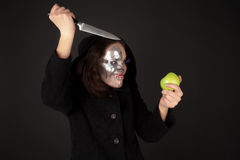 Two-faced witch with green apple and kitchen knife. Grimace Royalty Free Stock Images
