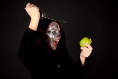 Two-faced witch with green apple and knife. Screaming Stock Photos