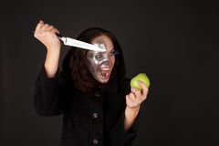 Two-faced witch with green apple and knife. Screaming Royalty Free Stock Images