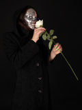 Two-faced witch holding the rose. Two-faced witch smelling the rose Stock Photography