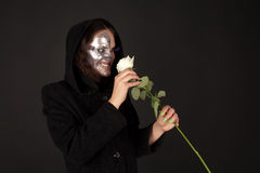 Two-faced witch holding the rose. On the black background Stock Photography