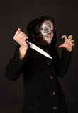 Two-faced witch with knife crinkled. On the black background Stock Photos