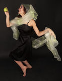 Two-faced woman with green apple dancing. Two-faced woman in bridal veiling with green apple dancing Stock Image