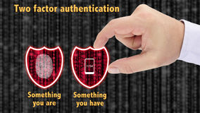 Two factor authentication shields concept have and are. Hand putting together two security shields revealing red datastreams showing the phrase something you are Royalty Free Stock Image