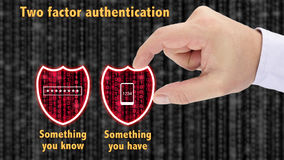 Two factor authentication shields concept have and know. Hand putting together two security shields revealing red datastreams showing the phrase something you Royalty Free Stock Photo