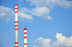 Two factory chimneys. With sky in the background Stock Photo