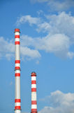 Two factory chimneys. With sky in the background Stock Images