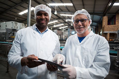 Two factory engineers with digital tablet smiling in the drinks production plant Royalty Free Stock Images