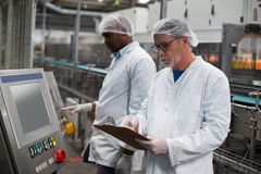 Two factory engineers operating machine in factory. Two factory engineer operating machine in drinks production plant Stock Photo
