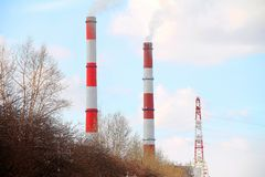 Two factory chimneys of them smoke royalty free stock photos
