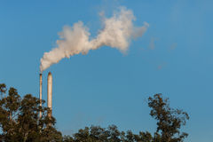 Two factory smokestacks with copy space. Two factory smokestacks with smoke against blue sky Royalty Free Stock Photo