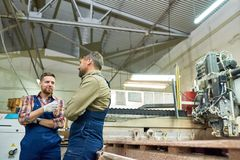 Two Factory Workers Chatting in Workshop. Portrait of two workmen chatting while operating machines in modern industrial shop standing by cutting unit, copy stock photo
