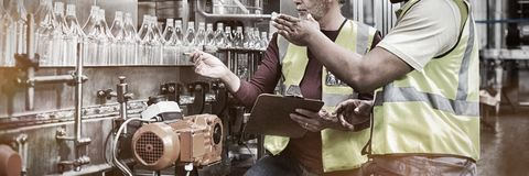 Two factory workers discussing while monitoring drinks production line. At factory royalty free stock photography