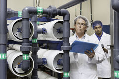 Two factory workers inspecting at bottling plant Stock Photos
