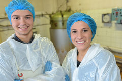 Two factory workers posing in front vats Stock Image