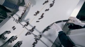 Two factory workers are sorting chocolate candies which are then moving in different directions. 4K stock video