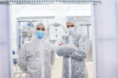 Two factory workers standing in protective clothes. Two crop sports nutrition production workers standing in protective clothing and looking at camera stock images