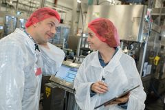 Two factory workers talking in factory. Two factory workers talking in a factory royalty free stock photo