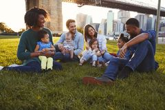 Two families with daughters sitting on lawn royalty free stock images