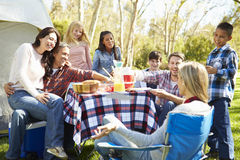 Two Families Enjoying Camping Holiday In Countryside. Sitting Relaxing Whilst Having A Picnic stock image
