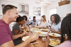 Two Families Enjoying Eating Meal At Home Together royalty free stock photos